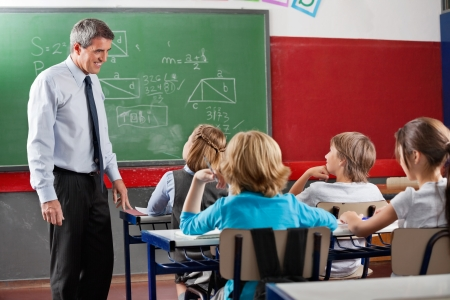 Side view of mature male teacher looking at students sitting in classroom Reklamní fotografie - 22614144