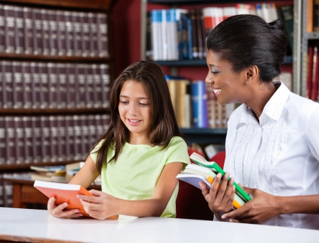 Happy young female librarian and schoolgirl looking together at book in library photo
