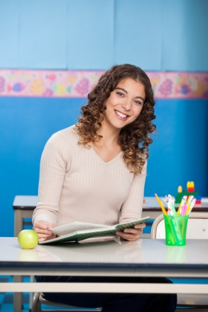 Portrait of young teacher with book sitting at desk in classroom photo