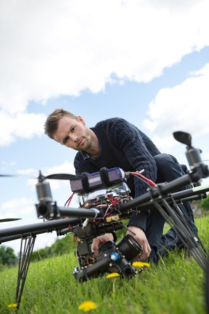 Portrait of young engineer fixing camera on UAV helicopter in park photo