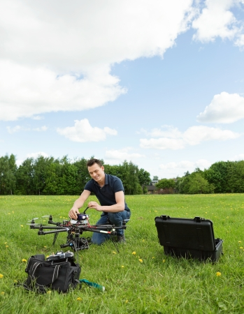 Young technician preparing multirotor helicopter in park photo