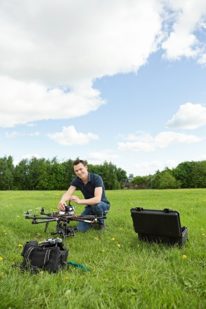 Portrait of young technician assembling UAV helicopter in park against cloudy sky photo