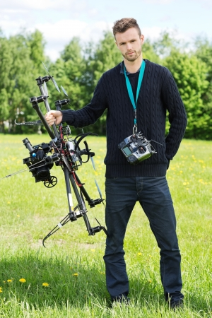 Portrait of young engineer standing with UAV drone and remote control in park photo