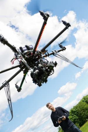 Low angle view of male engineer flying UAV helicopter with remote control in park photo