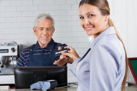 caja registradora: Retrato de mujer de mediana edad que da la tarjeta de crédito al cajero hombre en el mostrador de caja Foto de archivo