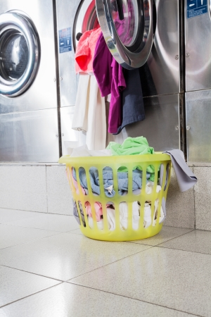 overflowing: Overloaded washing machine with laundry basket on floor at laundromat