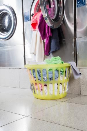 laundromat: Overloaded washing machine with laundry basket on floor at laundromat