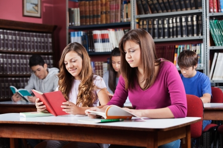 Male and female teenage students studying in library photo