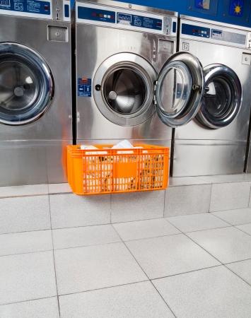 lavadora con ropa: Cesta de ropa mantiene frente a la lavadora abierta