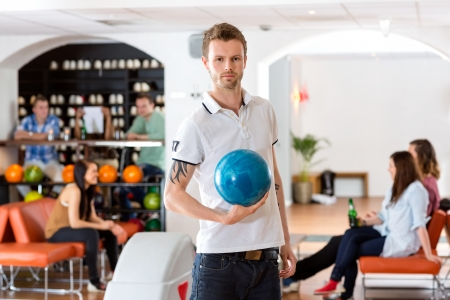 Portrait of confident young man with bowling ball while friends sitting in background at club photo