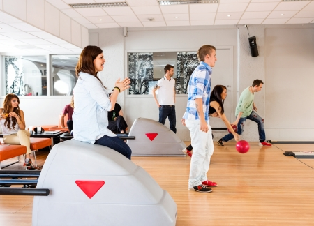 Group of young friends bowling together in club photo