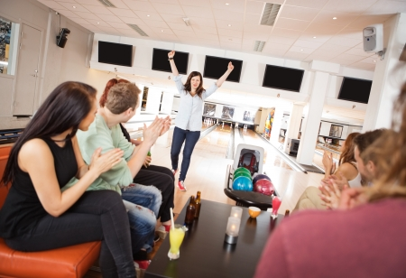 Young woman standing with arms outstretched while friends\ applauding in bowling club