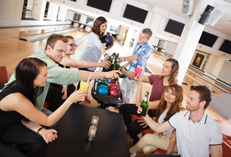 bowling alley: Group of young friends toasting drinks in bowling club