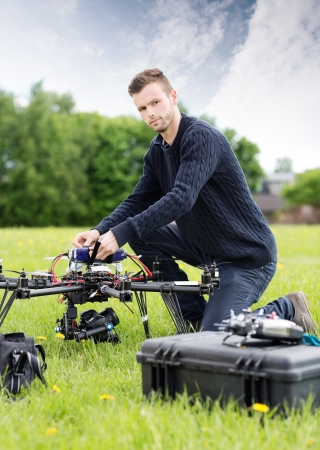 Portrait of confident young technician assembling UAV drone in park photo