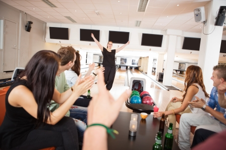 Group of friends applauding for woman in bowling club photo