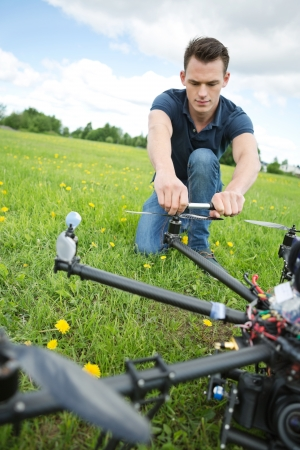 handtool: Young technician crouching while fixing propeller of surveillance drone in park Stock Photo