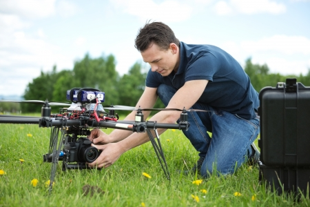 Young technician fixing camera on UAV helicopter in park photo