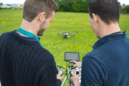 remote controls: Rear view of young engineers with remote controls and screen operating UAV helicopter in park