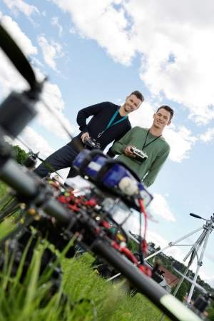Low angle view of young technicians standing with remote controls of UAV in park photo