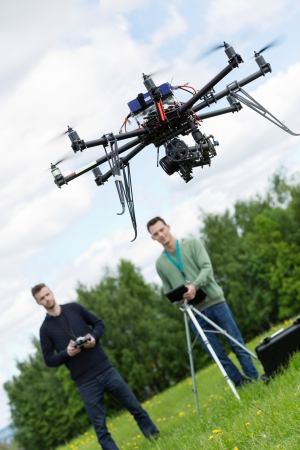 UAV octocopter flying with young engineers operating it in background at park Stock Photo - 22618715
