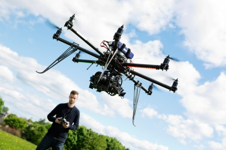 helicopter pilot: Young technician flying UAV drone with remote control in park