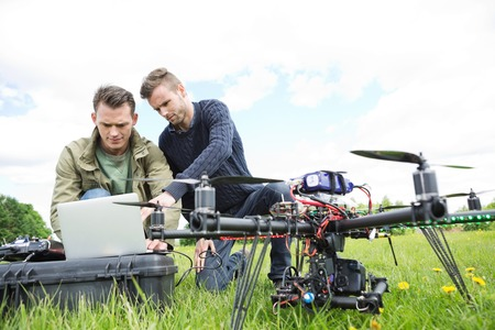 Young male engineers using laptop by UAV octocopter in park photo