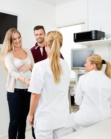 pregnant woman with husband: Young expectant couple visiting gynecologist at clinic