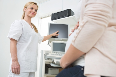 Young female doctor showing ultrasound scan to pregnant woman in clinic photo