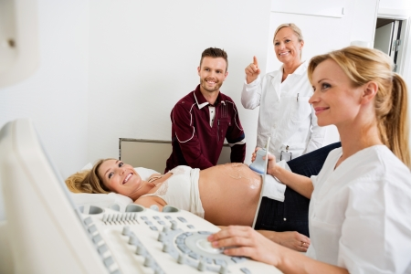 sonography: Young doctor checking pregnant woman while colleague and man looking at ultrasound machine