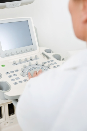 Midsection of female doctor using ultrasound machine in hospital photo