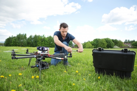 Young technician fixing propeller of UAV helicopter with handtool in park photo