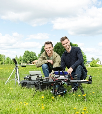 Portrait of happy male engineers with laptop and digital tablet by UAV at park photo