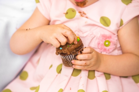 Midsection of birthday girl eating cupcake at home photo