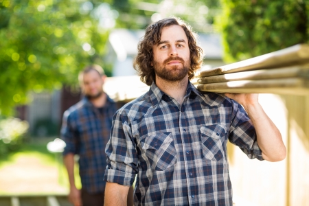 Mid adult carpenter with coworker carrying wooden planks outdoors photo