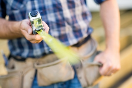 Cropped image of manual worker holding tape measure outdoors