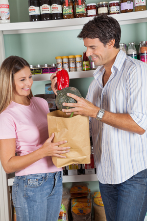 Happy mid adult couple shopping vegetables in supermarket