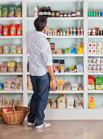 Full length rear view of thoughtful mid adult man looking at products in supermarket