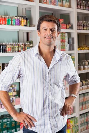 Portrait of handsome mid adult man standing with hands on hips in supermarket 版權商用圖片