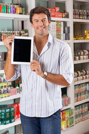 Portrait of handsome mid adult man showing digital tablet in supermarket