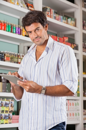 Portrait of handsome mid adult man with digital tablet in supermarket photo