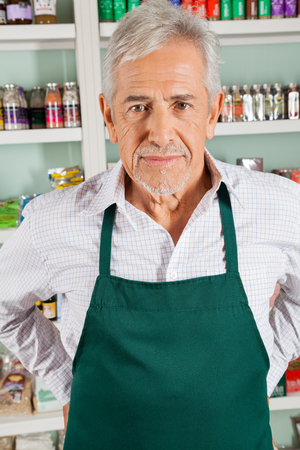 Portrait of confident senior male owner standing in grocery store