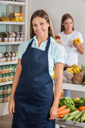 Portrait of mid adult saleswoman with female customer shopping in background at supermarket photo