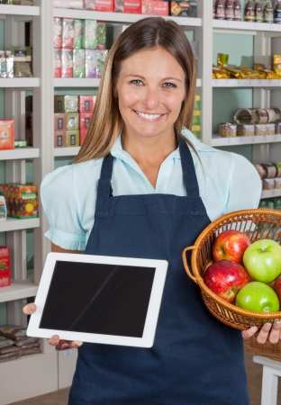 apple computer: Portrait of happy saleswoman holding digital tablet and fruits basket in grocery store