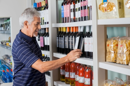 Side view of senior man choosing wine at supermarket photo
