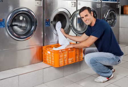 laundromat: Portrait of young man putting clothes in washing machine at laundromat