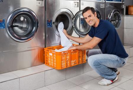 lavadora con ropa: Retrato de hombre joven que pone la ropa en la lavadora en lavandería Foto de archivo