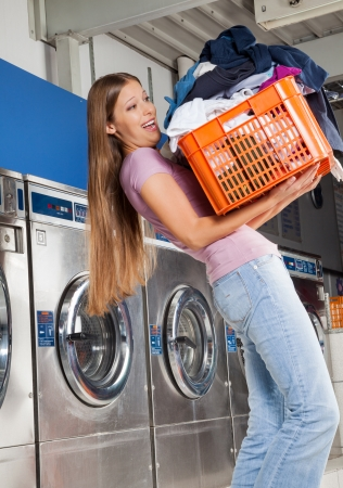 Side view of young woman carrying heavy basket of clothes in laundromat photo