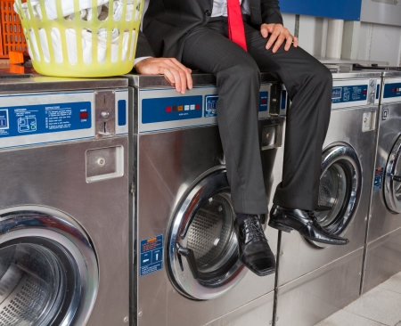 Low section of businessman with laundry basket sitting on washing machine at laundromat photo