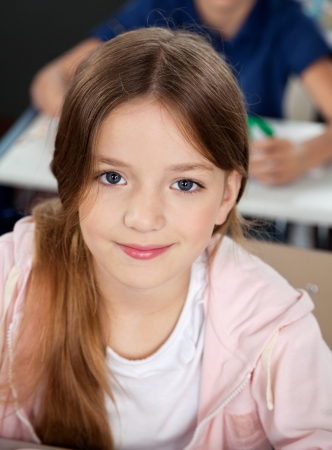 young schoolgirl: Closeup portrait of cute little schoolgirl in classroom Stock Photo