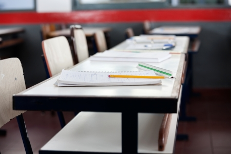 absence: Books and pencil on desk in classroom